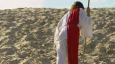 seigneur : Jesus Christ in robe and red sash walking through desert, looking at camera