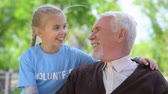 assistent : Happy child volunteer hugging male pensioner smiling each other, old people care Stockvideo