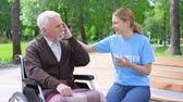 assistent : Happy young woman giving earphone old disabled man, supporting hospital patient Stockvideo