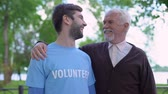 podporující : Young male volunteer and mature gentleman smiling to each other, social support
