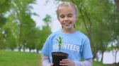 reforestation : Cheerful female kid holding plant smiling camera, natural resources conservation Stock Footage