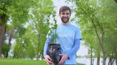 reforestation : Smiling male volunteer holding green tree seedling standing in forest, eco event Stock Footage