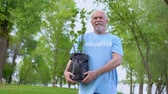 ответственность : Senior male volunteer holding plant seedling smiling camera, reforestation