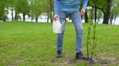 reforestation : Male eco activist watering tree by can, volunteer taking care natural resources