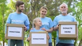 carità : Smiling volunteers holding donation boxes looking camera, charity project, help