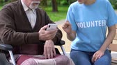 assistent : Female volunteer teaching old disabled man in wheelchair how to use cellphone Stockvideo