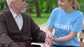 assistent : Smiling young volunteer supporting elderly disabled man in park, helping retiree