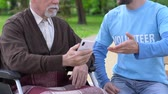 assistent : Male volunteer teaching aged man in wheelchair how to use smartphone, caregiving Stockvideo