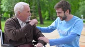 assistent : Male volunteer and elderly disabled man laughing in park, lonely pensioners care