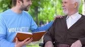 assistent : Kind male volunteer reading book to smiling old man in wheelchair, assistance