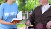 assistent : Sincere social worker reading book to disabled pensioner in park, volunteering