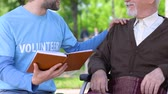 carità : Male volunteer reading book to lonely disabled pensioner in park, social support Filmati Stock
