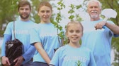 reforestation : Eco activists family holding trees saplings and shovel, nature conservation