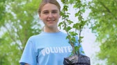 reforestation : Joyful blond woman holding tree sapling smiling on camera in park, eco volunteer