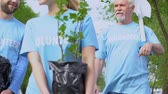 reforestation : Eco volunteers family with tree saplings and shovel walking in park, gardening