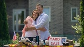 hirdetés : Happy couple selling old things on yard sale and hugging, american traditions