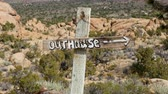 Zoom Out of Outhouse Sign que sopla en el viento - Desierto de Mojave - Riley's Camp