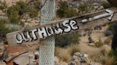Close up of Outhouse Sign blowing in the wind - Mojave Desert - Rileys Camp