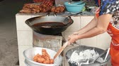 chop sticks : Woman prepares fried food on the street, unhealthy food