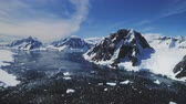 Aerial View: Mountain Panorama Drone Flight. Moving Ice Floes in the Calm Antarctic Sea. Reflection of Antarctica Rocks Ridge in Water Surface. Amazing View of Nature Landscape. 4k, UHD Footage