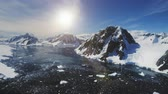 fotografando : Sunset Over Lemaire Channel. Antarctica Aerial Flight Over Polar Ocean, Snow Covered Mountains. Drone Overview Shot Of Polar Bay. Bright Sun Over Mighty Mounts, Ice Cold Ocean. 4k Footage. Stock Footage
