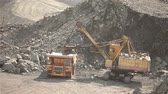 berendezés : The excavator and dumper in the quarry, Large yellow excavator loaded ore into a dumper Stock mozgókép