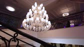 Luxury large crystal chandelier hanging in the Palace. Vintage lighting lamps with light bulbs and a lot of pendants. The rich interior of the hall of ancient ages. Vídeos