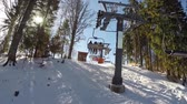 elevador : a ski lift carries people up on the mountain, Skiers descend from the snowy mountains, people are skiing, high spruces on the hillside, sunny day, Stock Footage