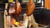roast ham : Large chunks of delicious pork hams cooked on an open fire. The street food. Food outdoors. Camping and cooking on a spit over the fire, man cooks large pieces of meat on a spit on fire, closeup