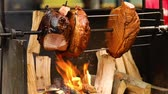 szynka : Large chunks of delicious pork hams cooked on an open fire. The street food. Food outdoors. Camping and cooking on a spit over the fire, man cooks large pieces of meat on a spit on fire, closeup