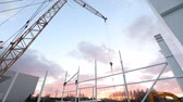sobreposição : Industrial exterior, Mounting of metal structures against the background of an orange sky with clouds, construction work, construction of an industrial building, timelapse Vídeos