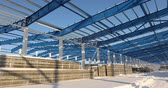 strukturální : Modern storehouse construction site, the structural steel structure of a new commercial building against a clear blue sky in the background, Construction of a modern factory or warehouse