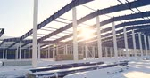 snowfall : Construction of a modern factory or warehouse, modern industrial exterior, panoramic view, Modern storehouse construction site, the structural steel structure of a new commercial building Stock Footage