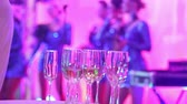 sax : Glasses with champagne on the background of silhouettes of womens music group, a female music band performs in a restaurant or hotel lobby