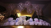 miś : Teddy bears sitting in a row, white teddy bears, helium balloons, cute teddy bear with a butterfly on her neck, soft toy, Interior halls for childrens birthday, a gift, a room, indoors, Teddy bear