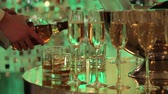 banquete : Glasses of champagne and wine on the buffet table, a bottle of champagne or wine in a bucket on a background of people dancing, blurred silhouettes of people Stock Footage