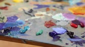 finger painting : Artist mixes paint on the palette, Art brush mixed paint on the palette, artist brush mix color oil painting on palette, artistic brush, hand close-up Stock Footage
