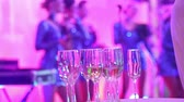неузнаваемый : Glasses with champagne on the background of silhouettes of womens music group, a female music band performs in a restaurant or hotel lobby