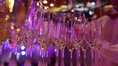 waiter : The waiter pours champagne in glasses, Glasses with champagne on the table in the restaurant, glasses of champagne on festive table, Clean glasses on a table prepared by the bartender for champagne