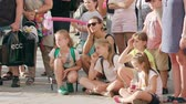 görme : Lublin, Poland - July 2018: A crowd of children sitting on the ground in town. Long shot. Soft focus