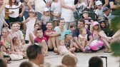 taps : Lublin, Poland - July 2018: A crowd of people sitting on the ground in town. Long shot. Soft focus