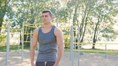 Male athlet does morning exercise outdoors close up slow motion. Workout standing on the is located near the lake with water and trees on the shore. Healthy lifestyle will power motivation concept Vidéos Libres De Droits