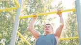 motivatie : Pull-up strength training exercise. Slim athlete a very fit guy fitness instructor or a personal trainer working out his arm muscles on outdoor beach gym as part of a crossfit workout.