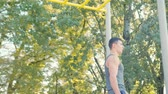 a small athlete resting after exercise Pull-up strength training exercise. Slim athlete a very fit guy fitness instructor or a personal trainer working out his arm muscles on outdoor Vidéos Libres De Droits