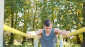 Male athlete performing difficult exercise on gymnastic parallel bars. Slim athlete a very fit guy fitness instructor or a personal trainer working out his arm muscles on outdoor beach gym as part of a crossfit workout.