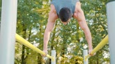 поднимать : Male athlete performing difficult exercise on gymnastic parallel bars. Slim athlete a very fit guy fitness instructor or a personal trainer working out his arm muscles on outdoor beach gym as part of a crossfit workout.