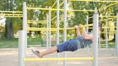 Handsome muscular man doing exercises on horizontal bar outdoors. Calisthenics workout. Slim athlete a very fit guy fitness instructor or a personal trainer working out his arm muscles on outdoor Vidéos Libres De Droits