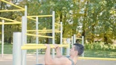Handsome muscular man doing exercises on horizontal bar outdoors. Calisthenics workout. Slim athlete a very fit guy fitness instructor or a personal trainer working out his arm muscles on outdoor Wideo