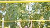 Pull-up strength training exercise. Slim athlete a very fit guy fitness instructor or a personal trainer working out his arm muscles on outdoor beach gym as part of a crossfit workout.