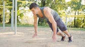motivatie : Push-ups strength training exercise. Slim athlete a very fit guy fitness instructor or a personal trainer working out his arm muscles on outdoor beach gym as part of a crossfit workout. Stockvideo